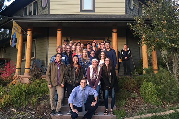 dean and students posing in front of home