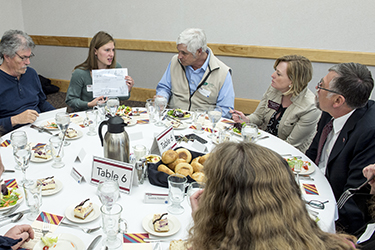 um president and students at a luncheon table
